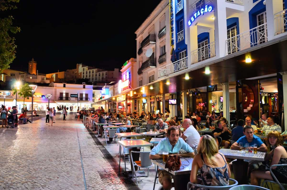 Bar with people at night in Albufeira Portugal.