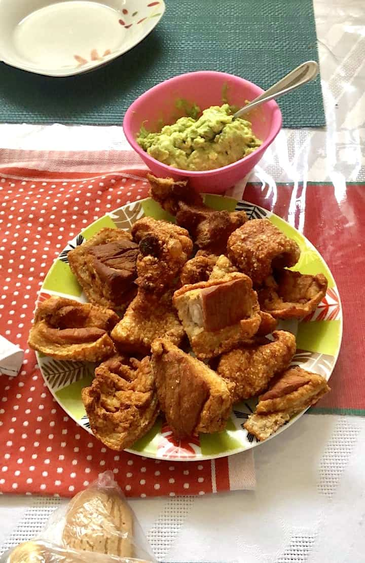 Crispy Guatemalan chicharrones on a plate with a bowl of guacamole.