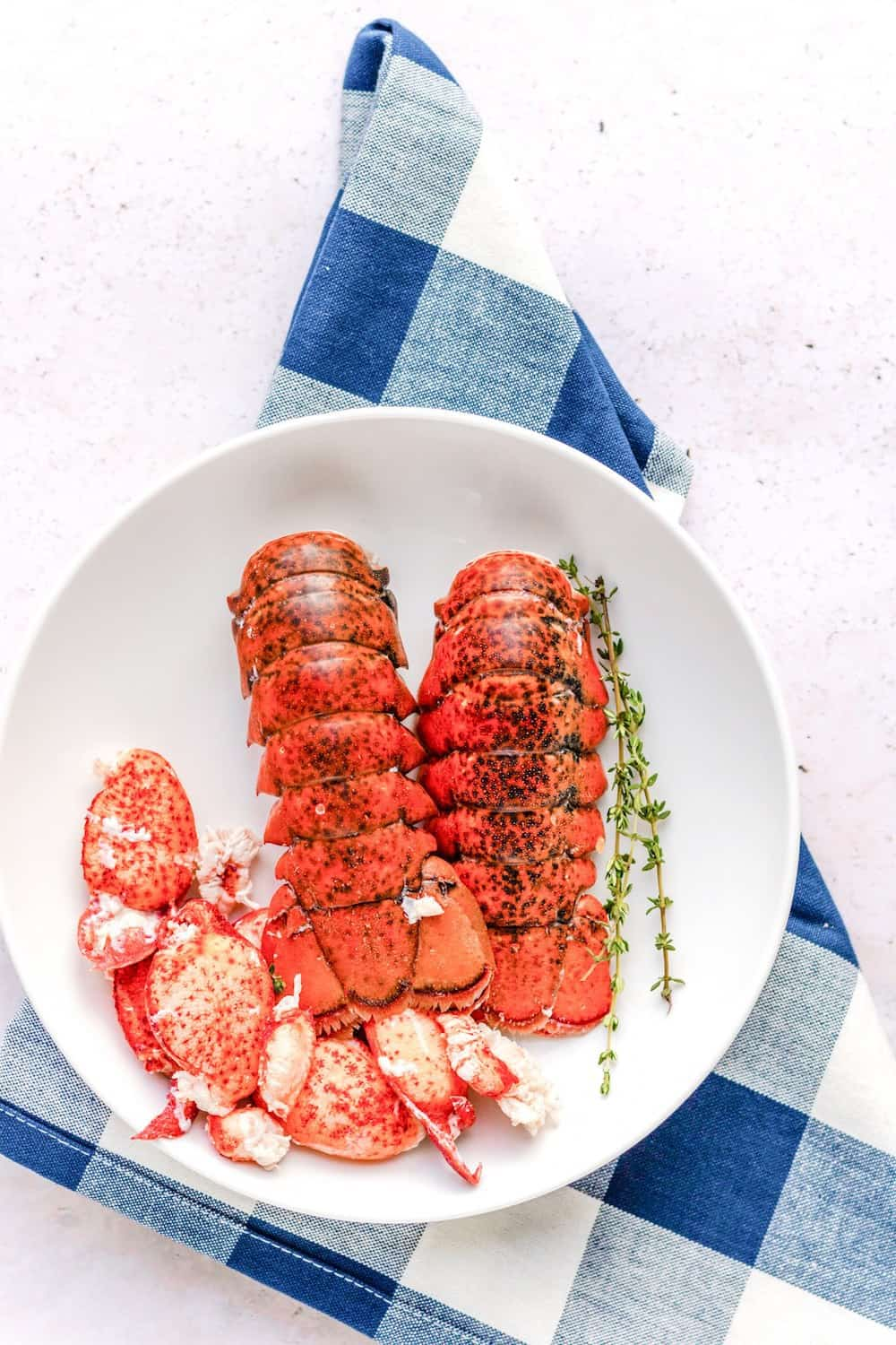 Cooked lobster tails and meat in a white bowl on a blue napkin.