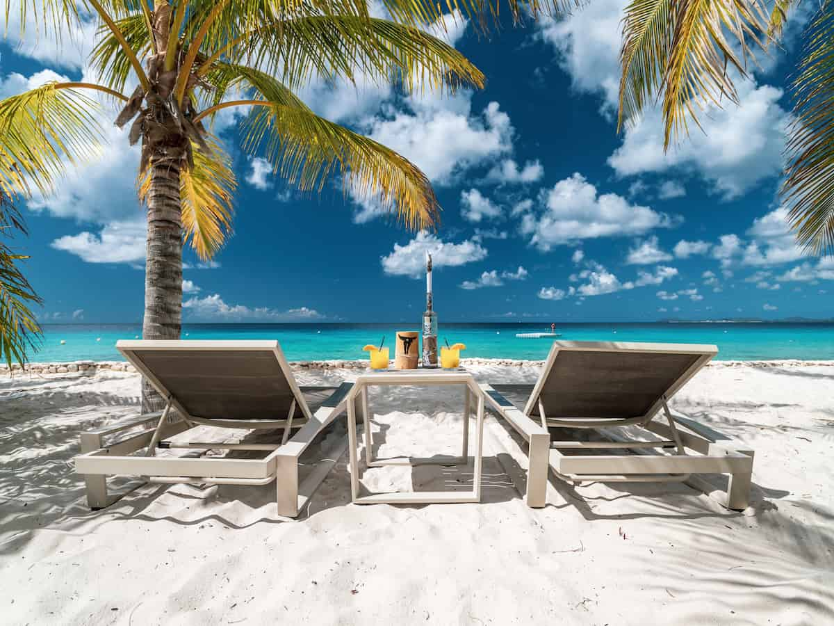 Two white loungers on a beach in Bonaire.