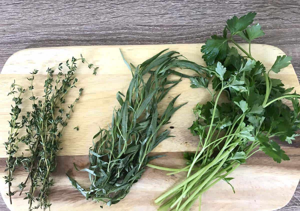 Thyme, tarragon and parsley on a wooden board. agon,