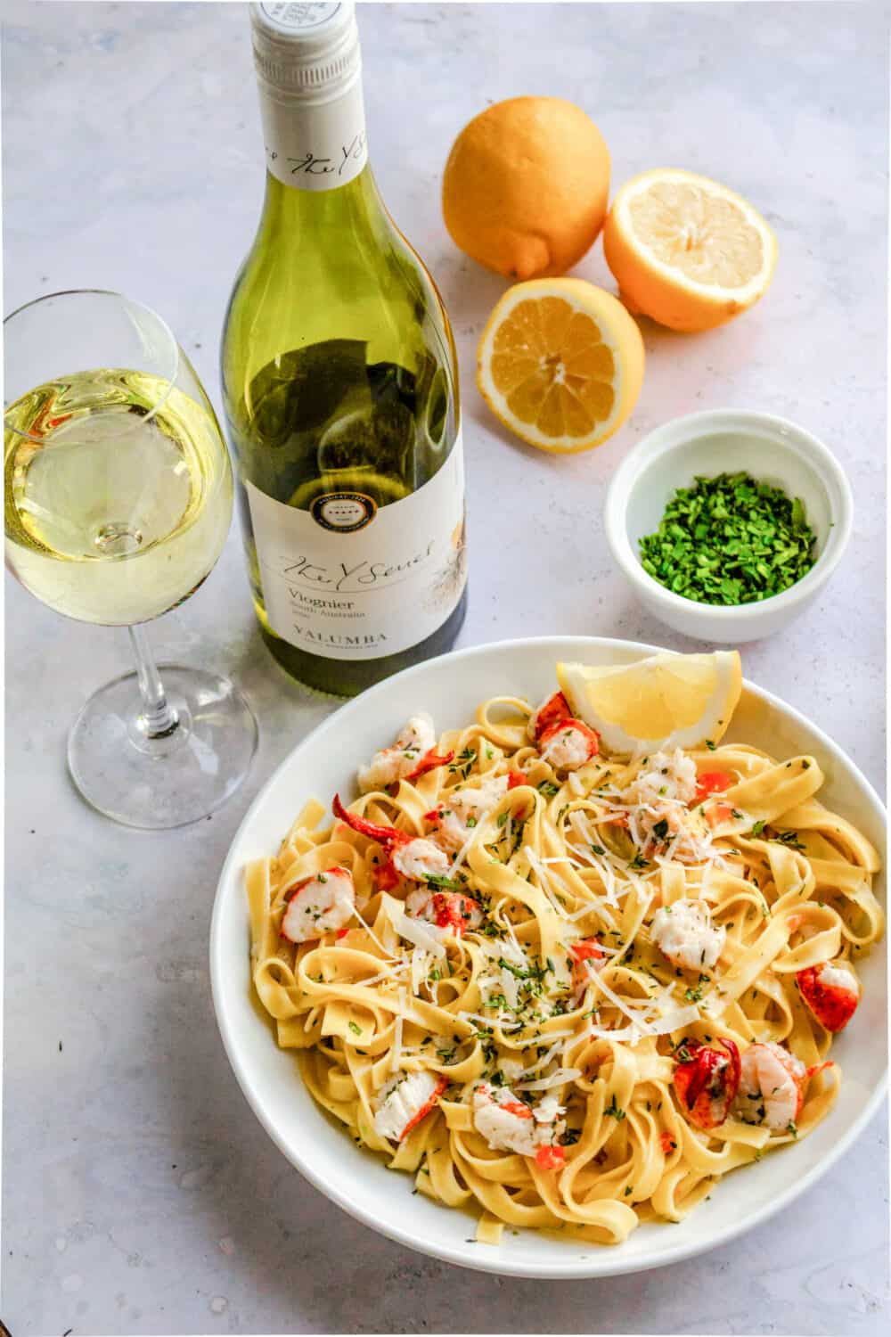 Lobster fettuccine in a bowl with a bottle of vigonier wine and wine glass. past