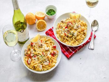 Two bowls of lobster fettuccine with a bottle of viognier wine.