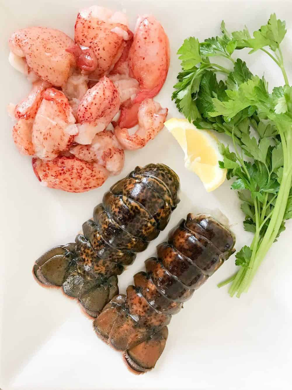 Lobster tails and lobster meat with parsley and lemon on a white plate.