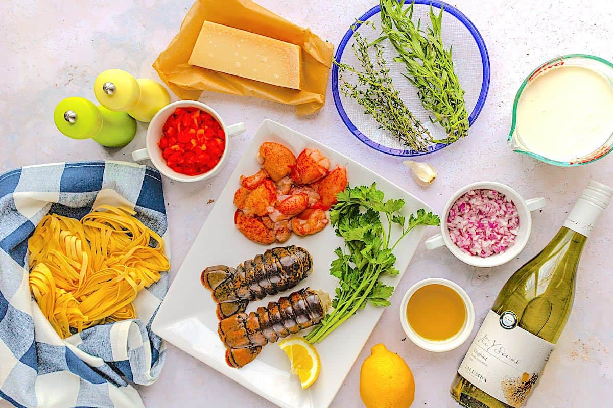 Overhead shot of ingredients for lobster pasta recipe include fresh herbs, lobster, red onion, garlic fettuccine, sweet red pepper, Yalumba Y Series viognier wine, lemon zest, heavy cream, parmesan and olive oil.