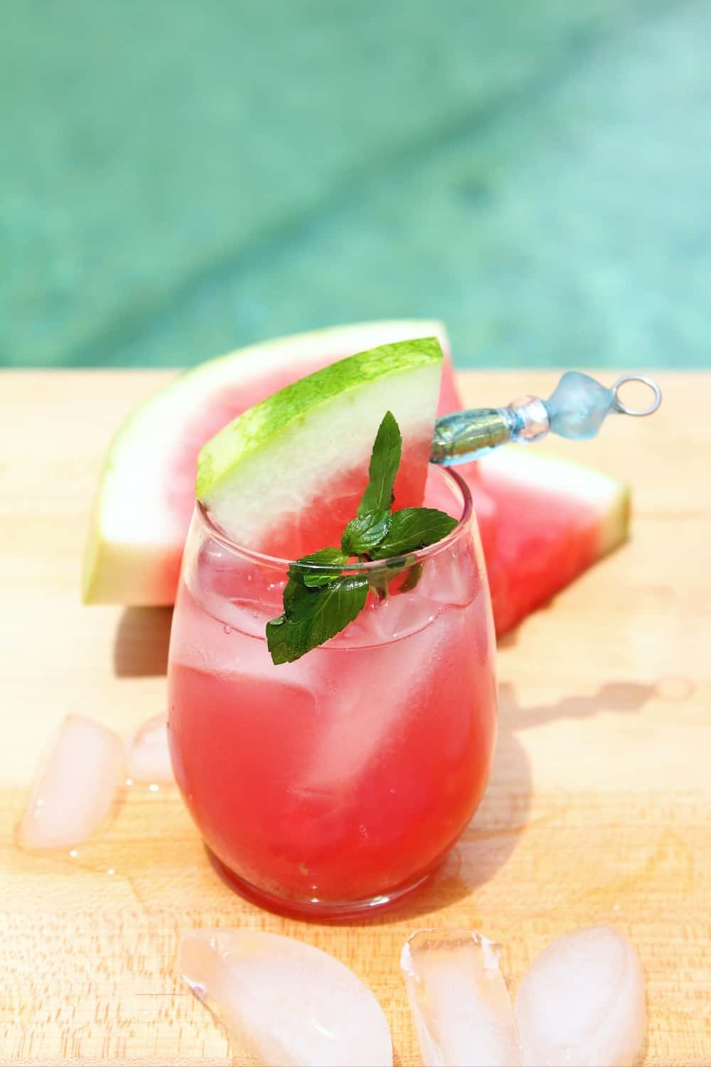 A watermelon drink with vodka in front of a swimming pool.