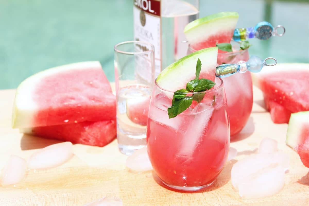 Bottle of vodka, a watermelon drink and slices of watermelon beside a swimming pool.