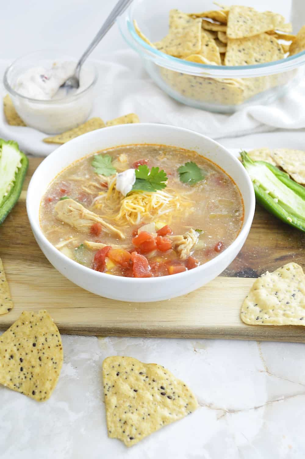 White bowl of crock pot chicken tortilla stew on a wooden board.