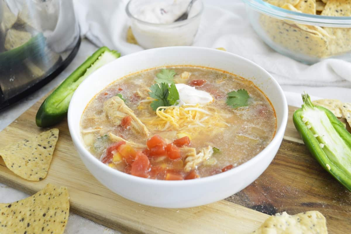 Bowl of Slow Cooker Chipotle Chicken soup on a wooden board.