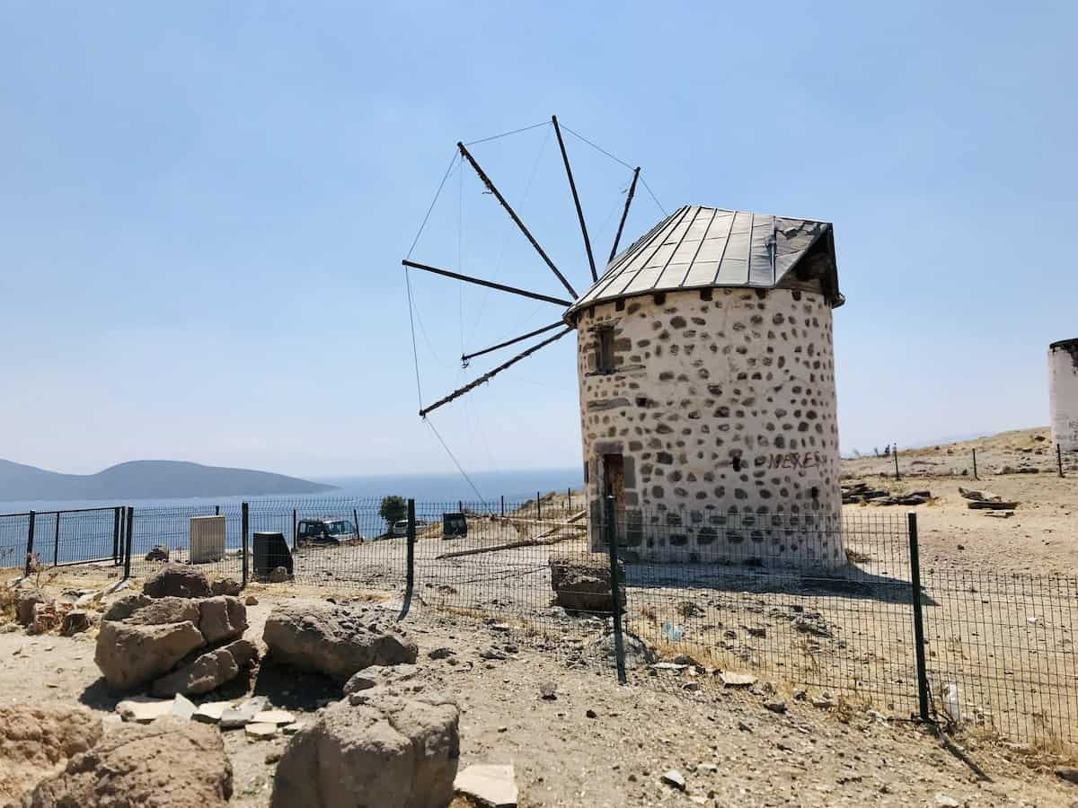 A stone windmill in Bodrum overlooking the sea.