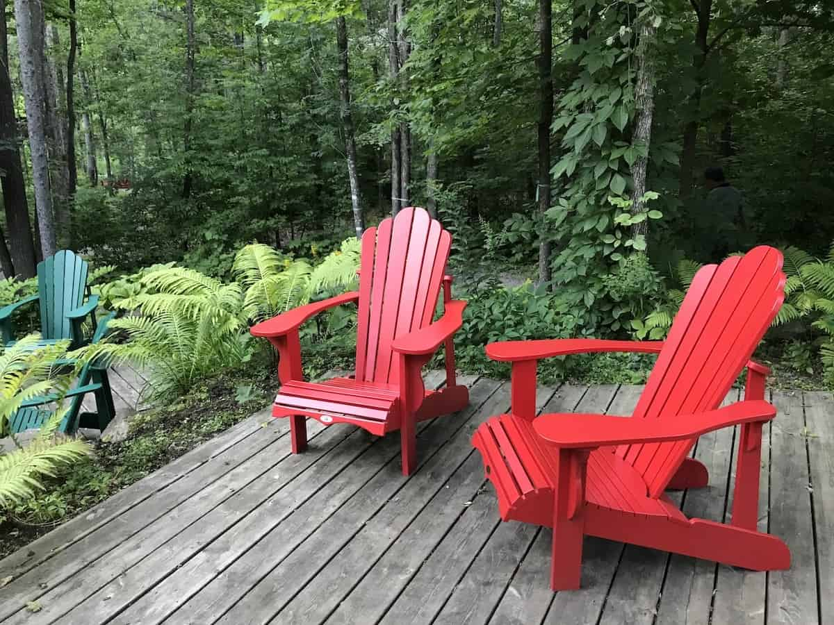 Two red chairs in the forest in Gatineau Park, Quebec.