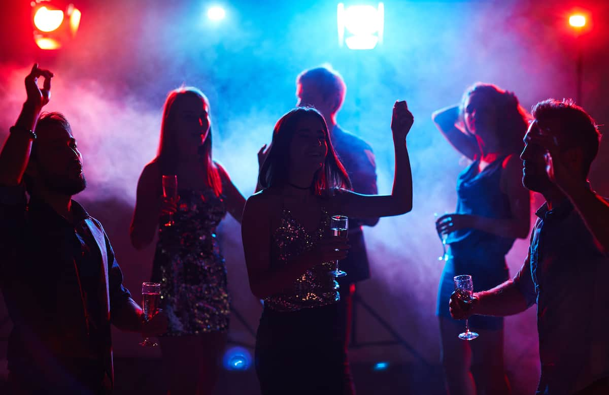 Silhouettes of young dressed-up people dancing in club smoke with glasses of champagne.
