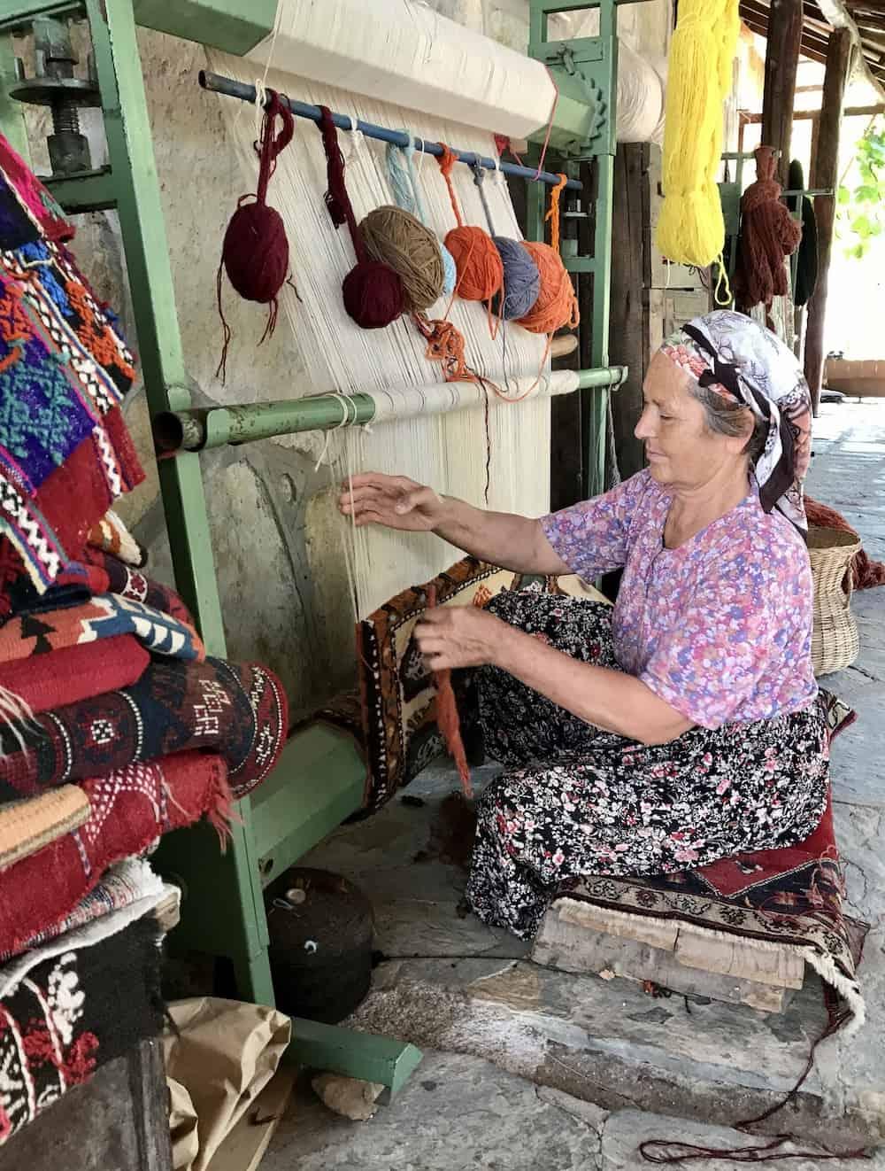Woman demonstrating weaving at Etrim Hali Carpet Cooperative.