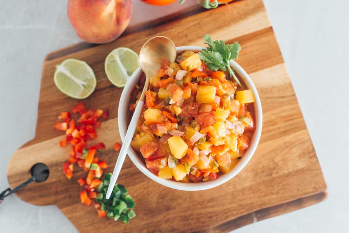 Fresh peach salsa in a bowl on a cutting board.