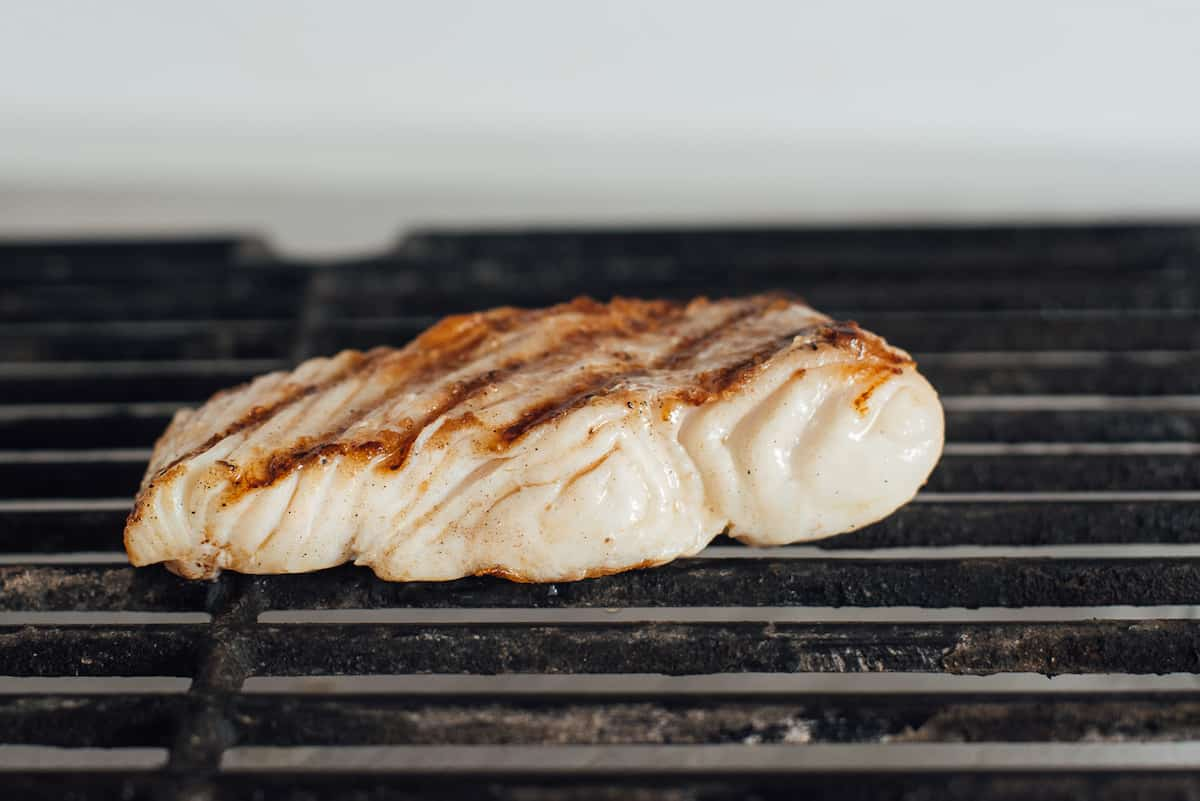 Halibut grilling on a barbecue. b