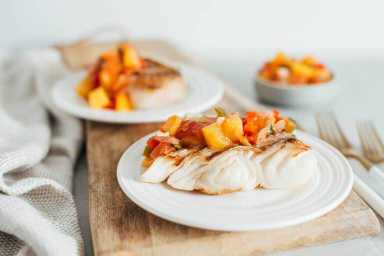 two pieces of grilled halibut with peach salsa on white plates.