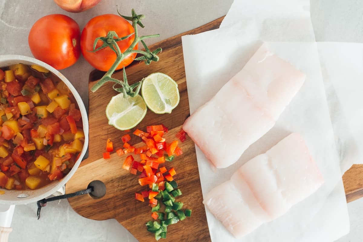 Tomatoes, peach and jalapeno peppers, lime and halibut ingredients.