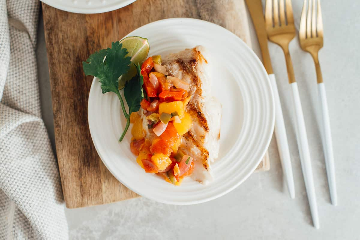 Overhead shot of grilled fish with peach sauce with cutlery..