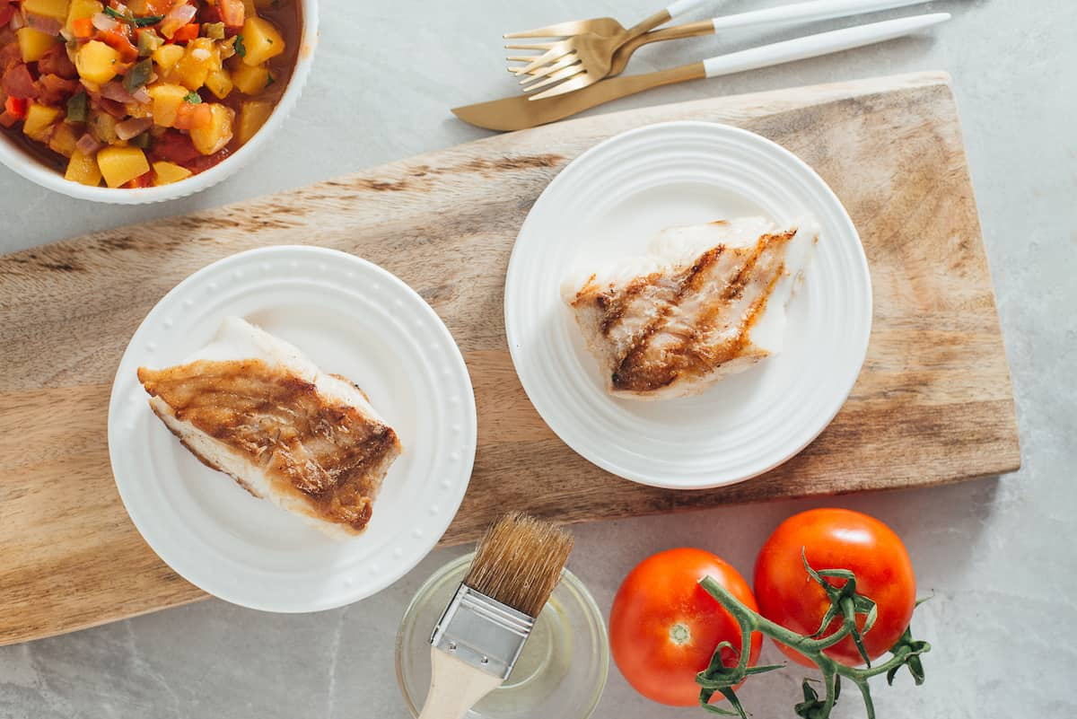 Portions of grilled halibut on white plates.