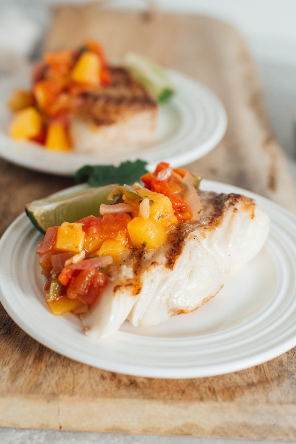 Portrait of two plates of grilled halibut with peach salsa on top.