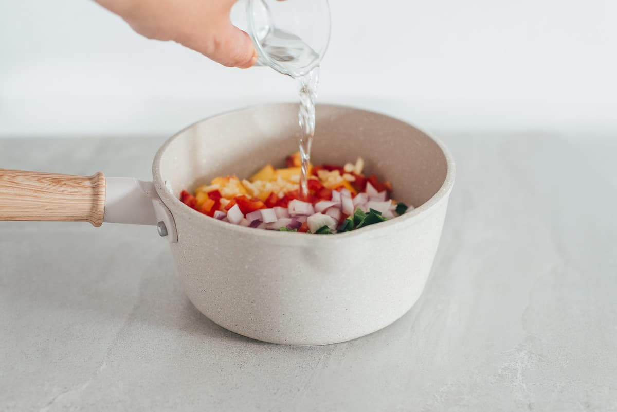 Pouring vinegar into a cooking pot to make peach salsa.
