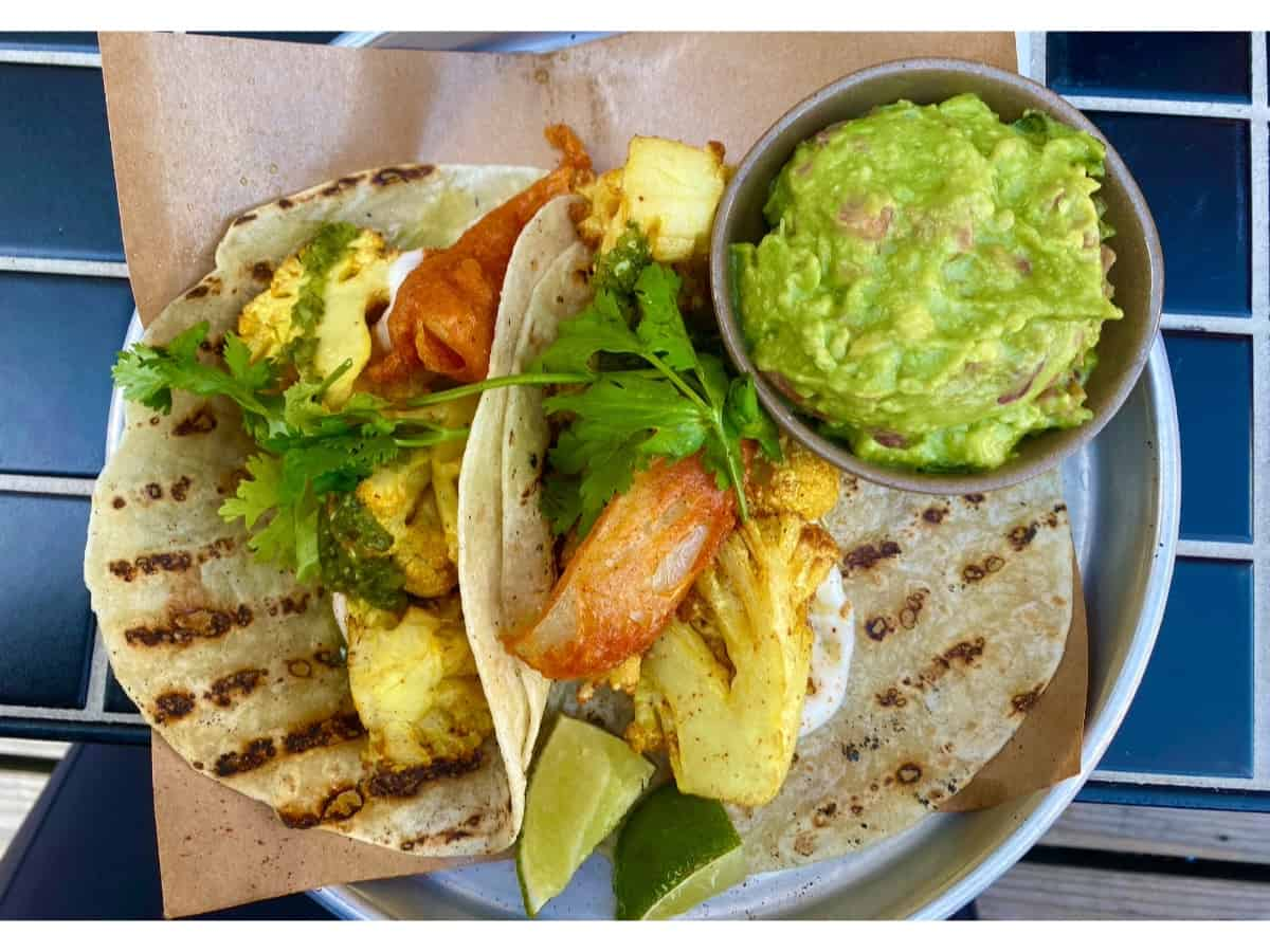 Two tacos with grill marks on a white plate with a side of guacamole.