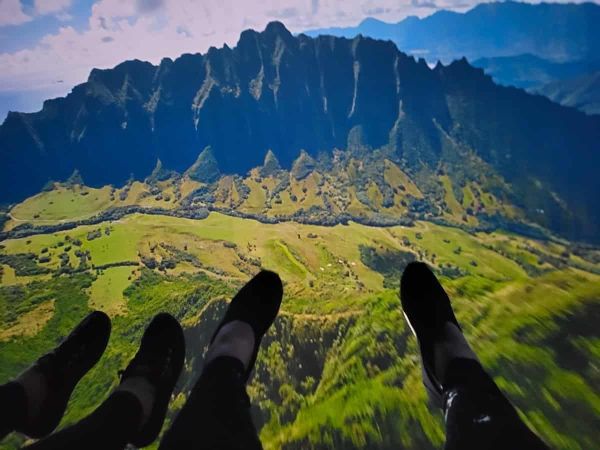 Zip lining over green fields in Hawaii with blue mountains in the background.
