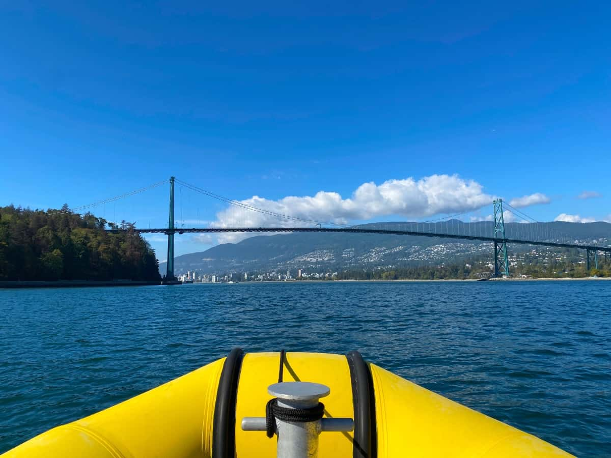 The view of a blue ocean from the bow of a yellow pontoon boat with a bridge in the background.